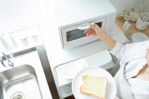 トースターでパンを焼く女性の写真素材 [FYI01462295]