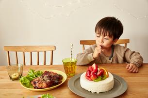 パーティーの準備がされているテーブルでケーキのクリームをなめる男の子の写真素材 [FYI01462302]