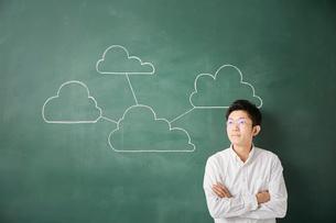 黒板に書かれた複数の繋がった雲の前で考える人のイラスト素材 [FYI01462309]