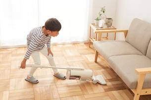 リビングの掃除をする男の子の写真素材 [FYI01462319]