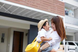 家の前で子供を抱っこする母親の写真素材 [FYI01462320]