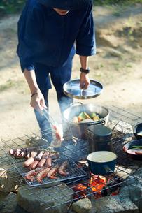 キャンプ場で食材を調理する女性の写真素材 [FYI01462343]