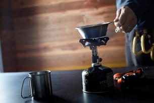山小屋の中の机でガスコンロを使い飲み物を温める人の写真素材 [FYI01462344]