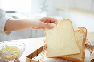 食パンを取る女性の手元の写真素材 [FYI01462372]