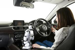 ロボットを使って自動運転車を操作する女性の写真素材 [FYI01462385]