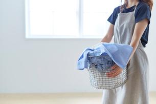 白い壁の前で籠いっぱいの洗濯ものを抱える女性の写真素材 [FYI01462399]