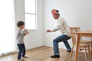 鬼役のお父さんに向かって豆まきをする男の子の写真素材 [FYI01462417]