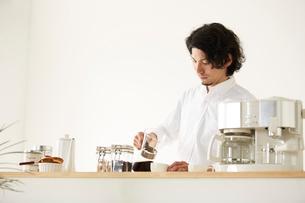キッチンカウンターでコーヒーを注ぐ男性の写真素材 [FYI01462432]