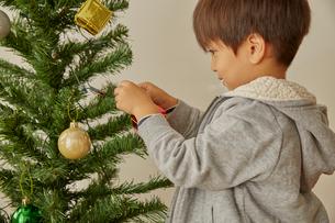 クリスマスツリーの飾り付けをする男の子の写真素材 [FYI01462448]