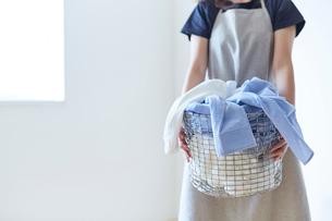 白い壁の前で籠いっぱいの洗濯ものを抱える女性の写真素材 [FYI01462455]