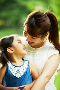 公園内でお母さんの膝の上に座って見つめ合う女の子の写真素材 [FYI01462457]