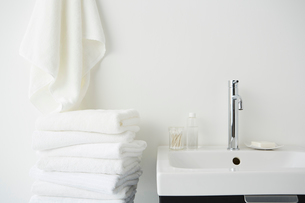 壁にかけられたタオルと畳まれたタオルと洗面台の写真素材 [FYI01462478]