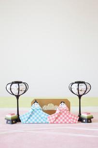 黄緑と白とピンクの和紙の上に置かれた折り紙で作った雛人形の写真素材 [FYI01462482]