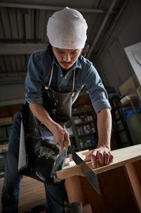 ノコギリで木材を切る人の写真素材 [FYI01462486]