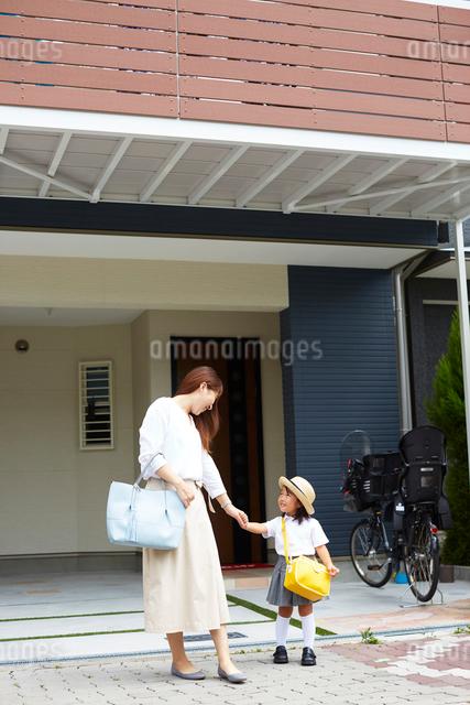 家の前で手をつないでいる親子の写真素材 [FYI01462505]