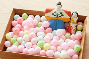 木天板の上にある器に入った雛人形とあられの写真素材 [FYI01462511]