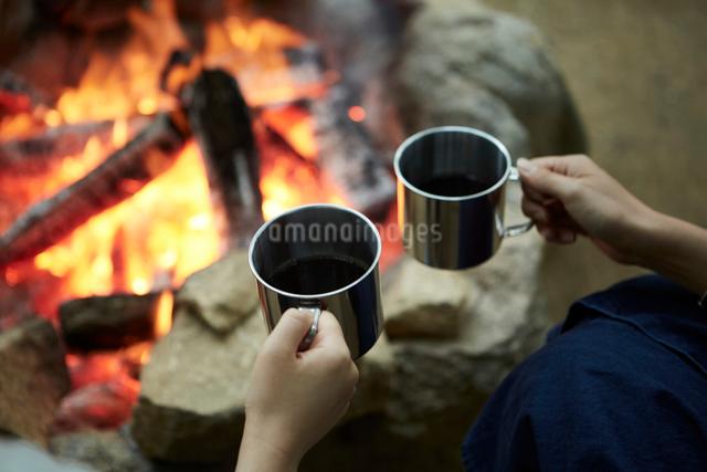 焚き火を囲ってコーヒーを飲む二人の写真素材 [FYI01462513]