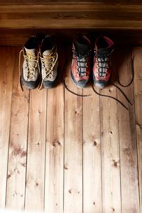 山小屋の中に置かれた紐をほどいた2足のトレッキングシューズの写真素材 [FYI01462518]