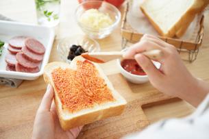 食パンにケチャップを塗る女性の手元の写真素材 [FYI01462521]