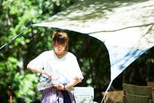 タープの横で袋から道具を出す女性の写真素材 [FYI01462535]