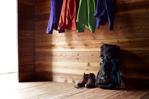 山小屋の中のフックに掛けられた4色の登山用ウェアと床に置いた靴とリュックの写真素材 [FYI01462542]