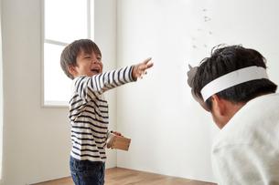 鬼役のお父さんに向かって豆まきをする男の子の写真素材 [FYI01462549]