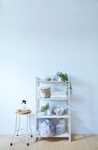 白い壁の前に置かれたランドリーラックとスツールの写真素材 [FYI01462571]