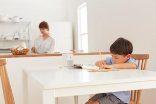 キッチンでお弁当を作る女性とダイニングで勉強する男の子の写真素材 [FYI01462580]