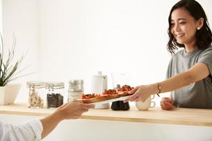 白いダイニングテーブルで食事する男女の写真素材 [FYI01462591]