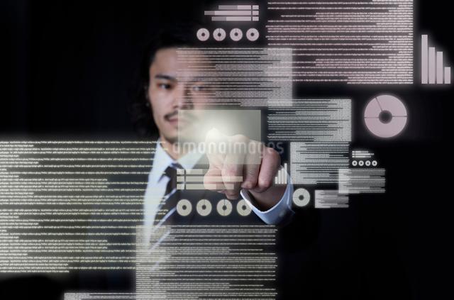 宙に浮いたデータをタッチするビジネスマンの写真素材 [FYI01462601]
