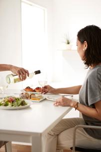 白いダイニングテーブルで食事する男女の写真素材 [FYI01462605]