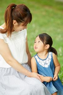 公園で隣り合わせで座って見つめ合うお母さんと女の子の写真素材 [FYI01462611]