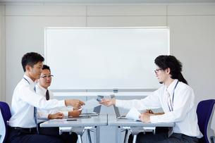 対面に座り書類を渡している社員の様子の写真素材 [FYI01462613]