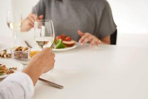 白いダイニングテーブルで食事する男女の写真素材 [FYI01462636]