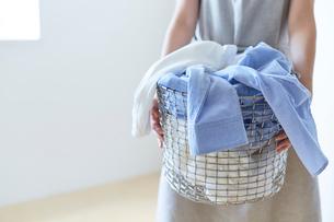 白い壁の前で籠いっぱいの洗濯ものを抱える女性の写真素材 [FYI01462641]
