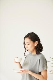 窓辺にたたずみコーヒーを飲む女性の写真素材 [FYI01462644]