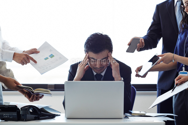 たくさんの人から用事を突き出されて悩む男性の写真素材 [FYI01462647]
