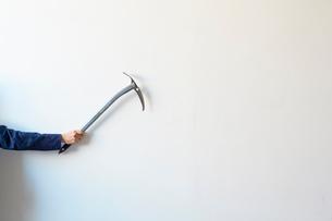 白い壁の前でピッケルを構える人の写真素材 [FYI01462676]