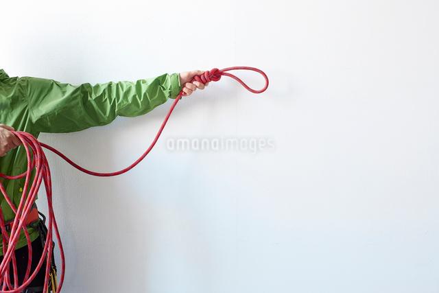 白い壁の前で結び目とまとまったをロープを持つ登山者の写真素材 [FYI01462705]