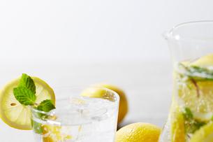 複数のレモンとレモンとミントと炭酸水の入ったガラスピッチャーとコップの写真素材 [FYI01462714]