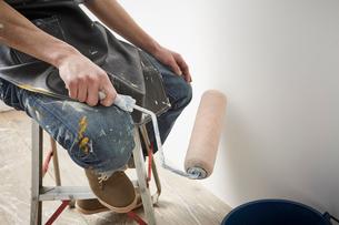 脚立に腰掛けてローラーを使う男性の写真素材 [FYI01462720]