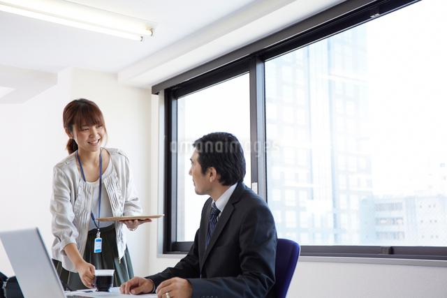 上司にお茶を配る女性の写真素材 [FYI01462727]