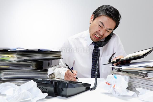 仕事が山積みのデスクで電話をするサラリーマンの写真素材 [FYI01462729]
