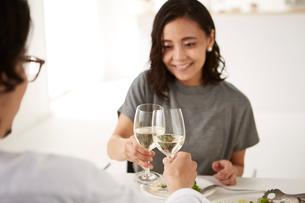 白いダイニングテーブルで食事する男女の写真素材 [FYI01462737]