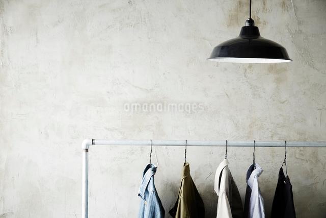 シルバーのラックにかかった服と照明の写真素材 [FYI01462765]