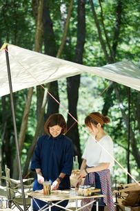 タープの下でキャンプご飯の支度をする女性2人の写真素材 [FYI01462770]