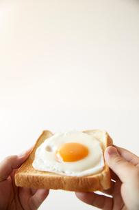 目玉焼きが乗ったトーストを持つ手の写真素材 [FYI01462772]