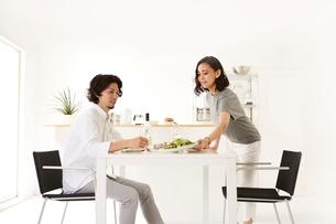白いダイニングテーブルで食事する男女の写真素材 [FYI01462776]