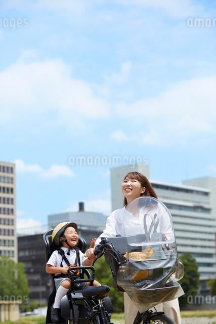 子供を自転車に乗せて出かける母親の写真素材 [FYI01462821]