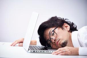 ノートパソコンに顔をつけて倒れこむ男性の写真素材 [FYI01462847]